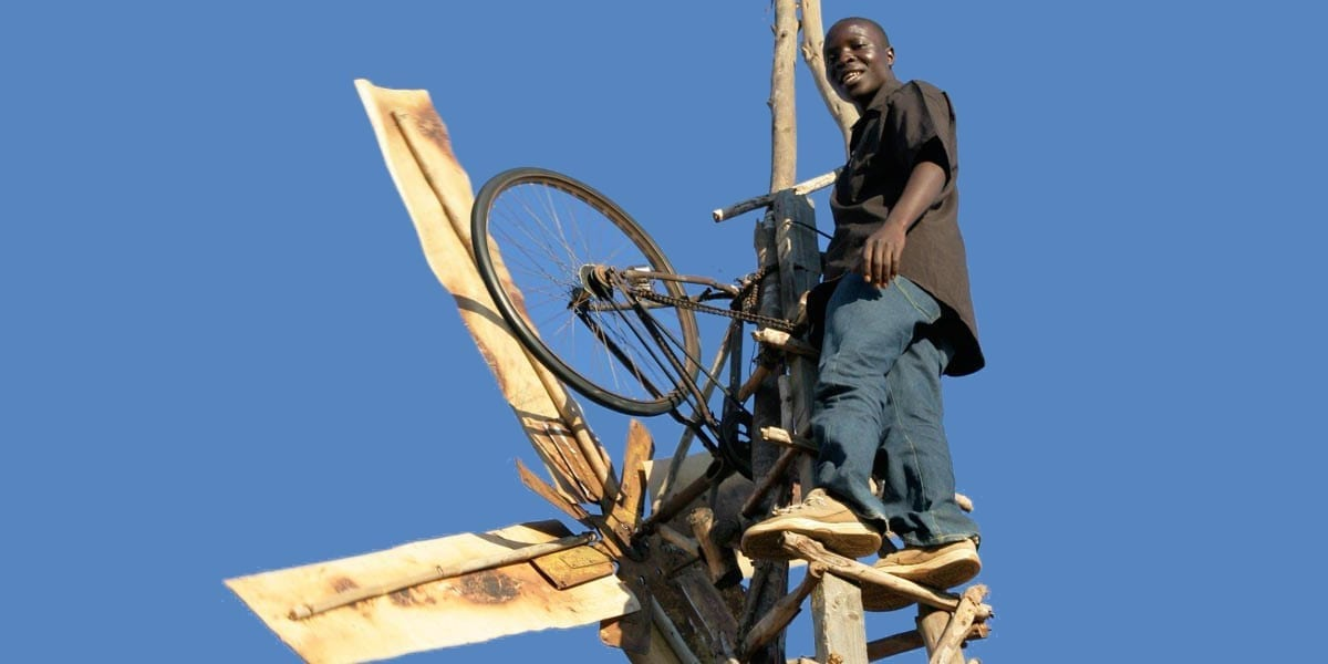 Kamkwamba up in his wind turbine power generator made from bicycle parts