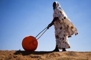 "A woman in El Fasher, North Darfur, uses a Hippo Water Roller, a device for easily and efficiently carrying water. The ""hippo roller"", with its large drum capacity (usually 75 litres), frees women and children from having to spend a large portion of every day dedicated to collecting water for their households. The African Union-United Nations Hybrid Operation in Darfur (UNAMID) has distributed some 30,000 such rollers across Darfur. Photo by United Nations Photo / Flickr"